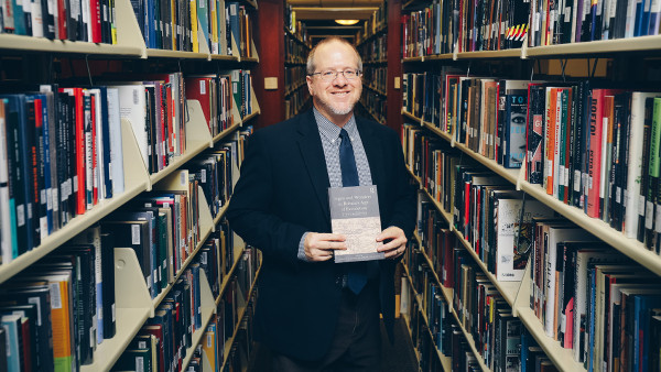 Professor of History Tim Fehler holds a sourcebook he co-authored with Abigail Hartman