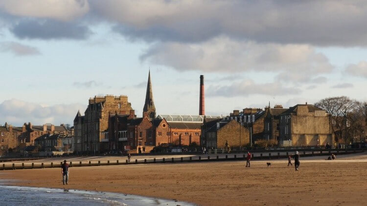 handheld-stabilized-shot-of-edinburghs-portobello-beach-with-people-dogs-landmark-buildings-at-the-back-edinburgh-scotland-uk_h2gntxfqx_thumbnail-full01