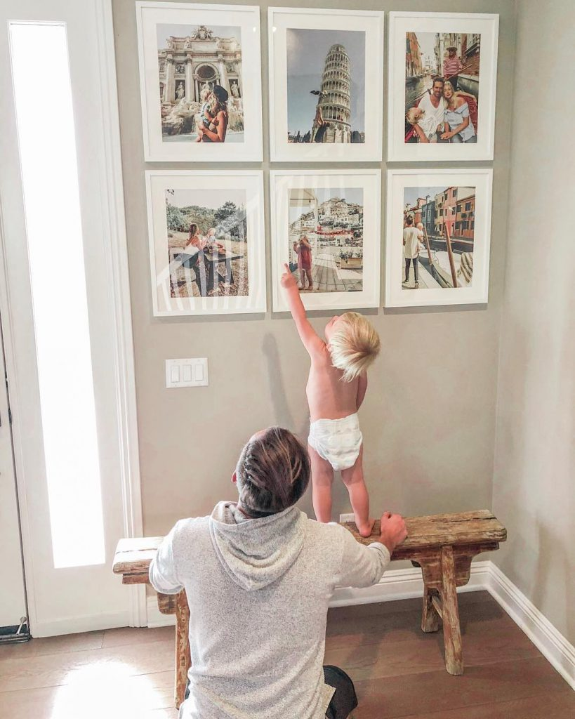 baby with gallery wall