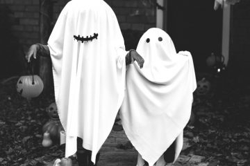 Two kids dressed as ghosts on Halloween