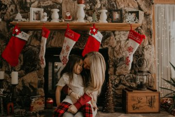 Mom and daughter in front of the fireplace during Christmas