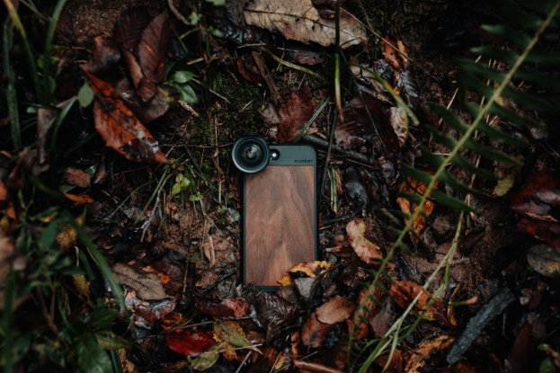 Smartphone sits in grass with Moment phone camera lens on it