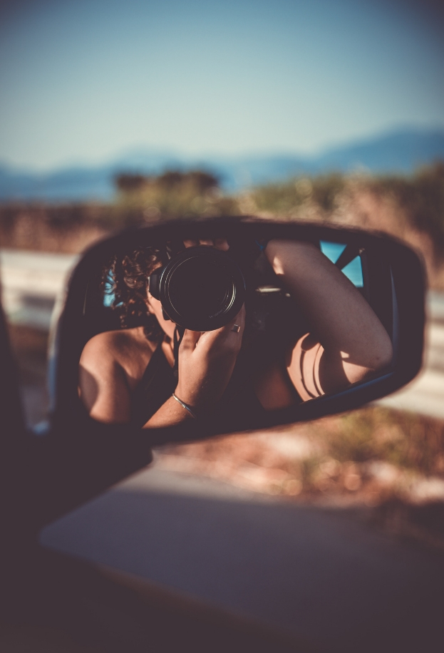Photographer takes self-portrait in passenger side mirror in moving car