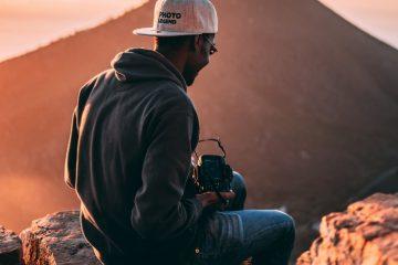 Photographer sits atop a rock