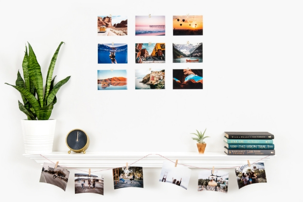 Prints on wall in grid and hanging from shelf with twine