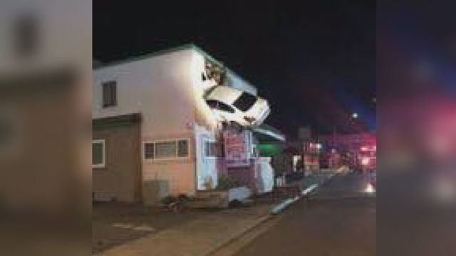 Speeding auto  flies into second floor of building