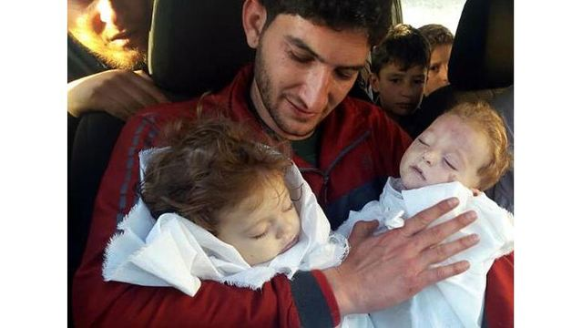 Heartbreaking photo shows father saying goodbye to twins after Syria chemical attack