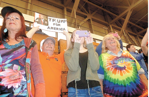 Supporters of Donald Trump hold up signs and take photos and videos on their phones during the President-elect's campaign rally at the Crete Civic Center in Plattsburgh in April. (Enterprise photo — Antonio Olivero)