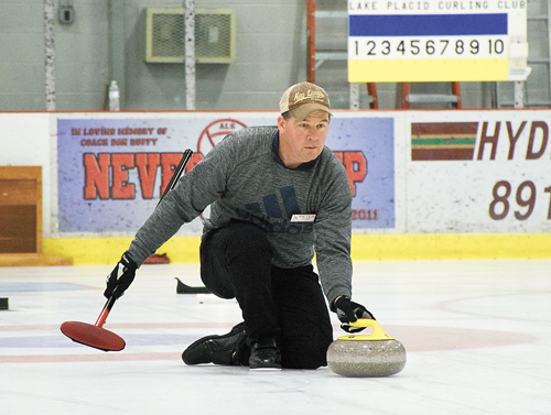 Peter Clark slides on one knee as he releases a stone at a recent Lake Placid Curling Club learn-to-curl event in Saranac Lake. (Enterprise photo — Justin A. Levine)