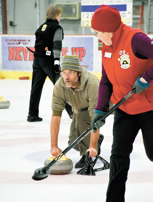 Mark Hofschneider of Saranac Lake gets ready to release a curling stone at the Saranac Lake Civic Center. (Enterprise photo — Justin A. Levine)