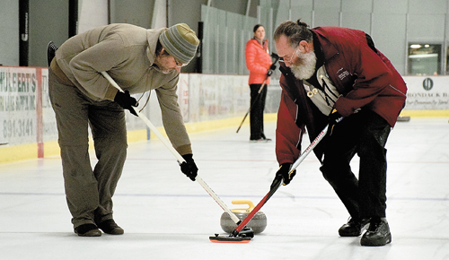 Mark Hofschneider and Tom McKernan sweep in front of a stone as it makes its way down the curling sheet. (Enterprise photo — Justin A. Levine)