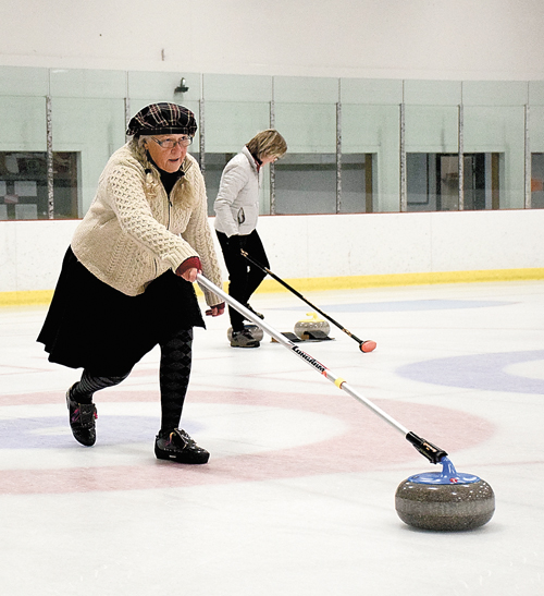 Amber McKernan uses a handle to slide a curling stone down the ice. She said the handles are good for people who have trouble launching a stone the more traditional way. (Enterprise photo — Justin A. Levine)