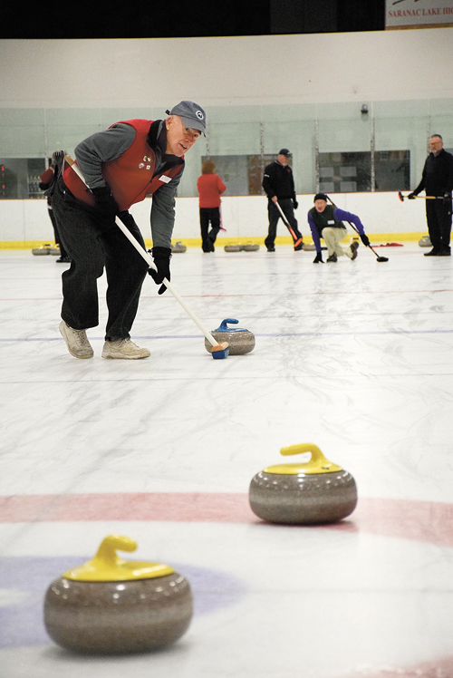 Roger  Steinbrueck of Saranac Lake has been curling for about a decade. Here, he sweeps in front of a stone thrown by John Crawford of Queensbury. (Enterprise photo — Justin A. Levine)