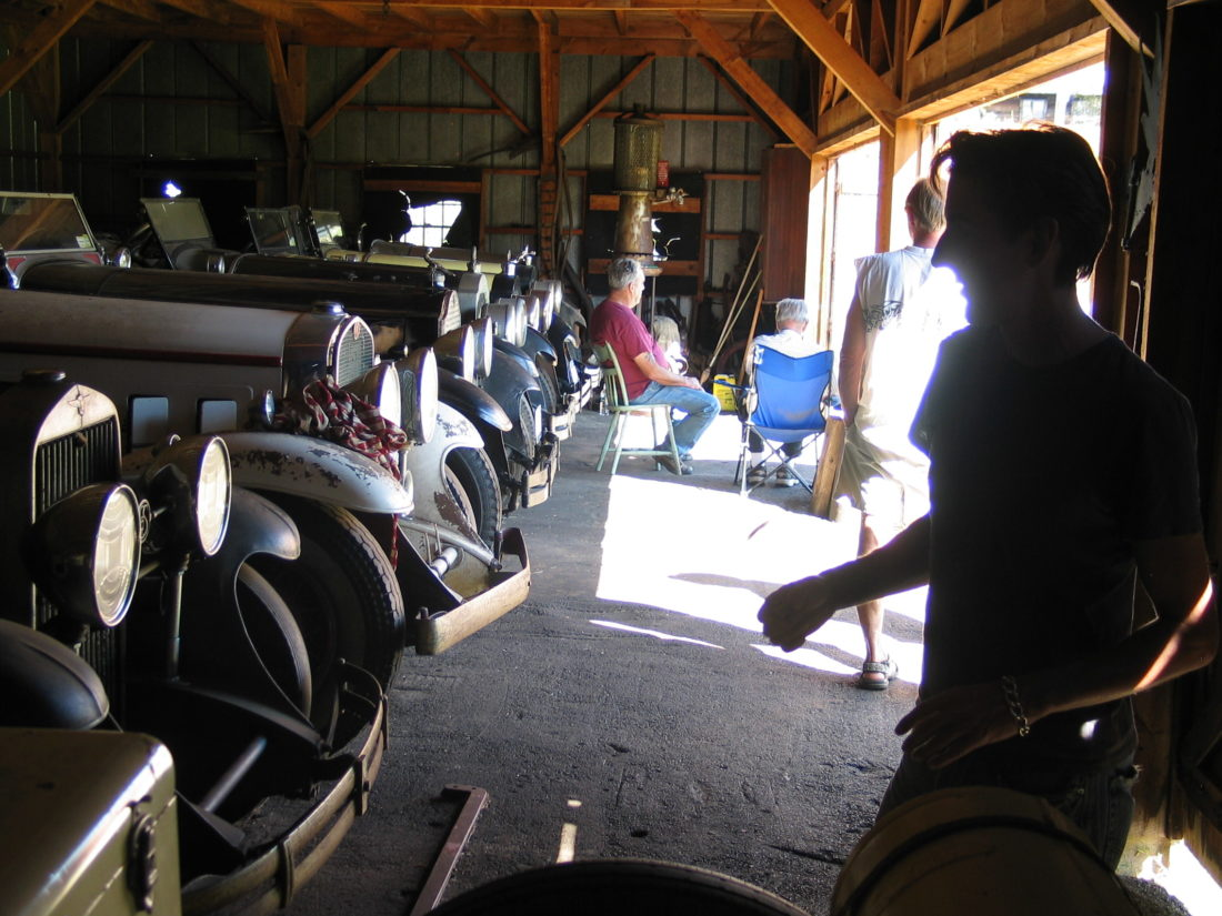 "Visitors check out Packards and other antique cars inside a barn owned by John ""Hawkeye"" Hawkinson in September 2010. (Enterprise photo — Peter Crowley)"
