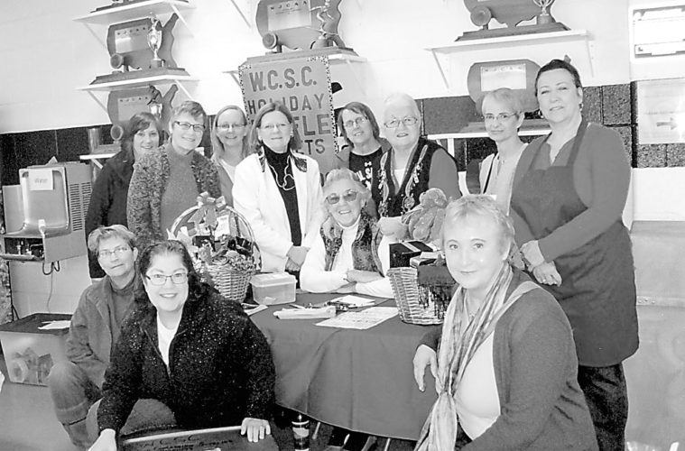 Women's College Scholarship Club members are shown with two holiday gift baskets each filled with about 25 gifts. Back row from left are Jill Zagrobelny, Susan Alexander, Hannah Marlow, Linda Jackson, Deb Naybor, Elaine Holmlund, Siobhan Crary, and Heidi Gutersloh. Front are Kathy Root, Donna Fulkerson, Gloria Drucker and Candy Wagner. The baskets included Adirondack gifts, stocking stuffers and holiday specialty food items. Raffle tickets sold briskly at the NCCC and Sparkle Village craft shows, raising funds for scholarships for local high school and continuing education students. The drawing was held Dec. 3 at the conclusion of Sparkle Village. Sue Goetz won Basket No. 1 and Mary Ellen Henry won Basket No. 2. Both are from Saranac Lake. Gloria Drucker and Linda Beairsto were event chairs. They thank club members for donating basket items and all who purchased tickets to help local students. (Photo provided)