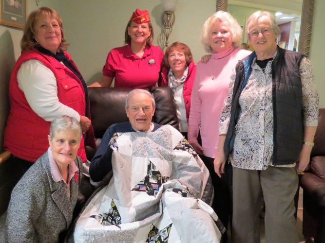 Frederick Mader, center, receives a U.S. Army Lap Robe from the Mountain Mama Quilters and the Adirondack Leatherneck Detachment of the Marine Corps League. Pictured from left to right with Frederick Mader are: Marcia Gilbert, Donna Sloan, Lisa Tubridy, Adirondack Leathernecks, Diane Reandeau, Diane Loeber and Judy Vaughn. (Photo provided)