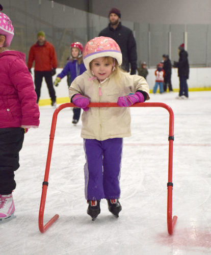 Mia Nason uses a pusher to practice ice skating during the St. Bernard's School's skating party Thursday at the Saranac Lake Civic Center. (Enterprise photo — Justin A. Levine)