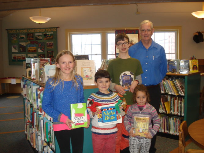 Local Home School Students who participated in the November Reading Challenge are shown holding a favorite book at the Saranac Lake Free Library. From left are Olivia Marocco, Oliver Halasz, Galen Halasz and Emma Gnann, with library Director Peter Benson. Skyler and Summer Cranker and Harper Gnann also took part in the Challenge. (Photo provided — Pat Wiley)