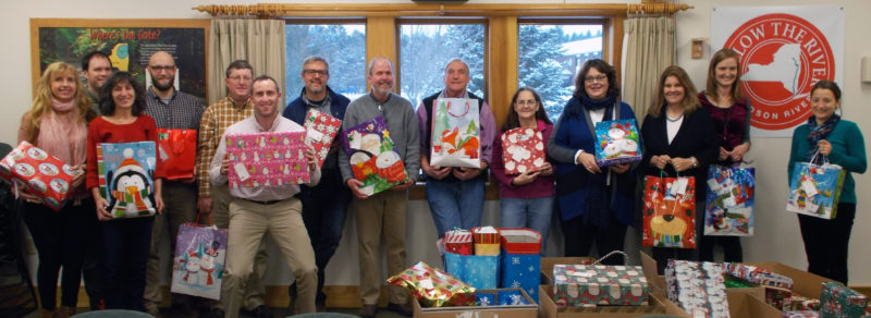 Adirondack Park Agency staff holds gifts they contributed to the 2016 Holiday Helper program. (Photo provided)