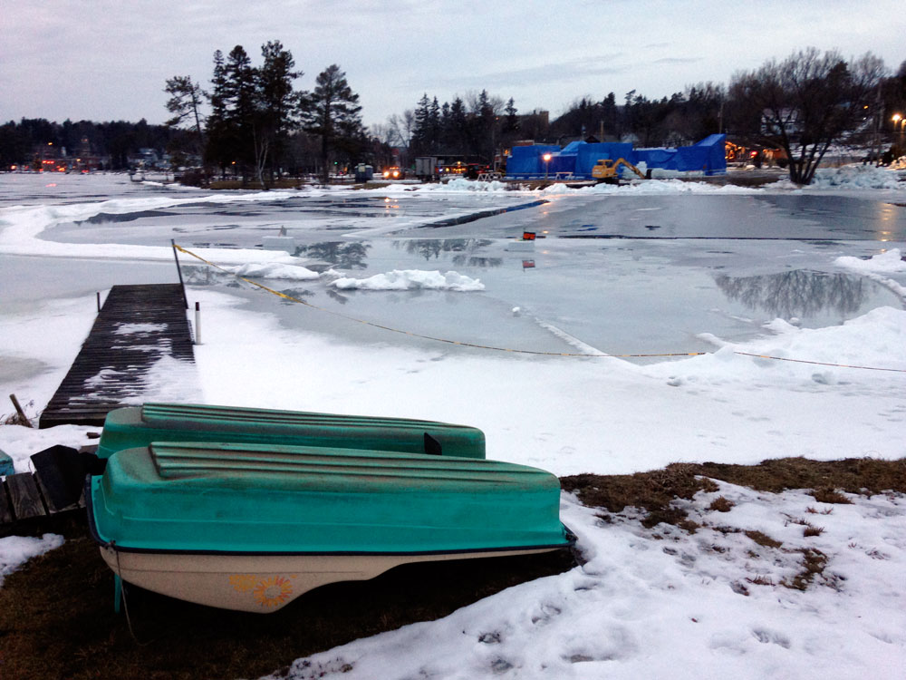 Snow and ice in and around Pontiac Bay on Lake Flower melt on this warm day in late January, as the Saranac Lake Winter Carnival Ice Palace was draped in blue tarps to protect it from the weather. (Enterprise photo — Peter Crowley)