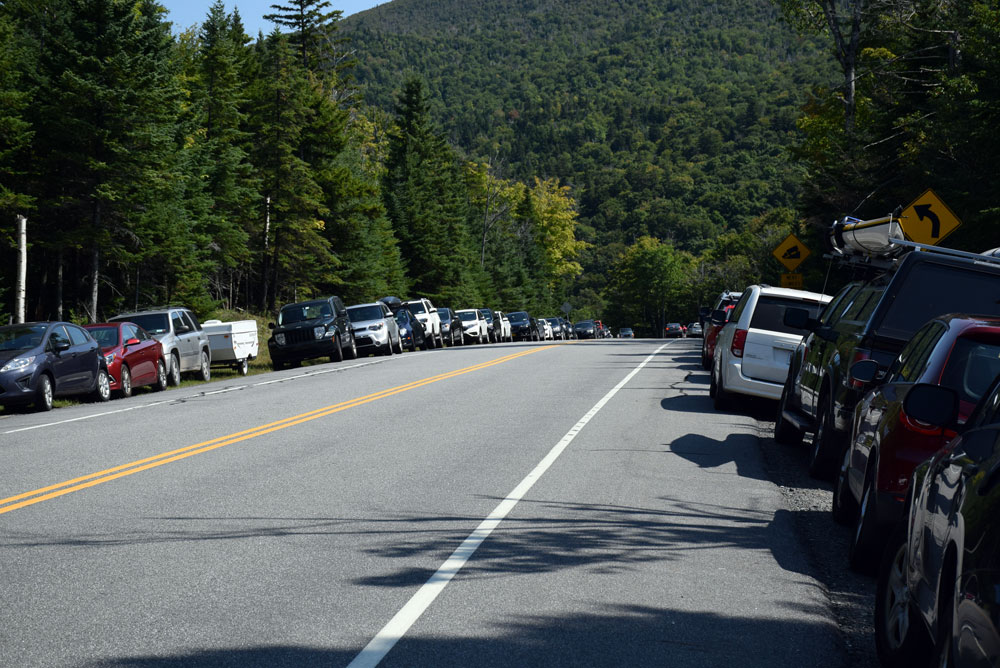 Dozens of cars park along state Route 73 near the trailheads leading to Pitchoff, Cascade and Porter mountains in Keene on Labor Day weekend. (Enterprise photo — Justin A. Levine)