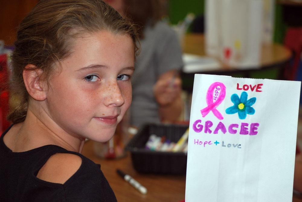 Petrova Elementary School student Phoebe Glennon holds up the luminary bag she decorated Sept. 9 in memory of Gracee Jewtraw. (Enterprise photo — Chris Knight)