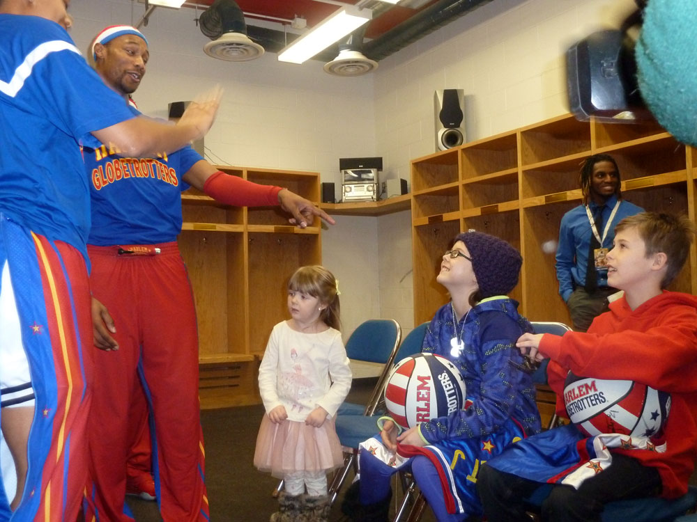 Members of the Harlem Globetrotters meet with Gracee Jewtraw, center, and her twin brother Noah Jewtraw in February at the Herb Brooks Arena in Lake Placid. (Enterprise photo — Antonio Olivero)