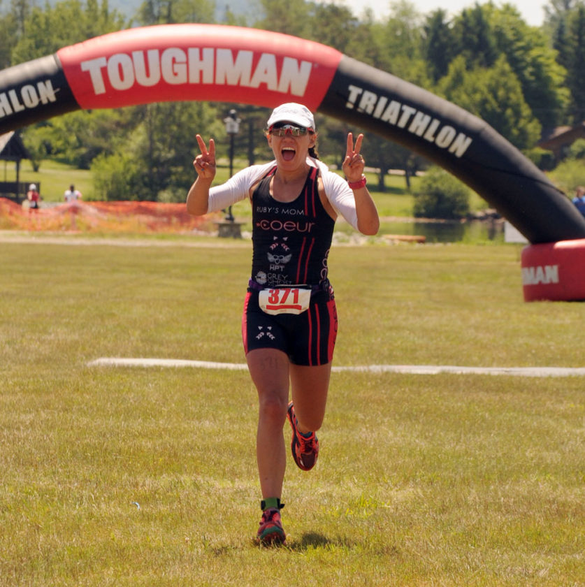 Amy Farrell of Tupper Lake crosses the finish line of the Toughman Tinman Triathlon in her hometown. (Enterprise photo)