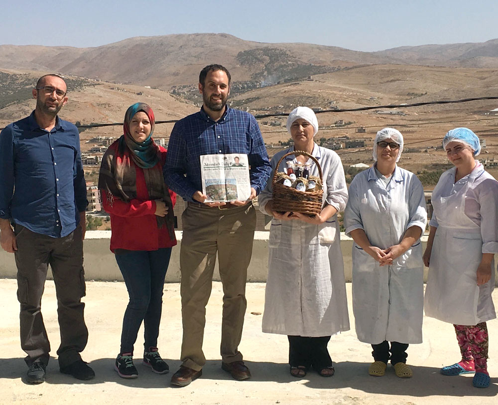 Saranac Lake resident Ezra Schwartzberg, holding a copy of the Enterprise, stands with (right) members of the Morning Star Cooperative in El Mhaidthe, Lebanon, and (left) employees of the Lebanon Reforestation Initiative. The employees presented Schwartzberg with a gift of products produced by the cooperative using herbs and agricultural products grown by local producers or foraged on the village's public lands. (Photo provided)