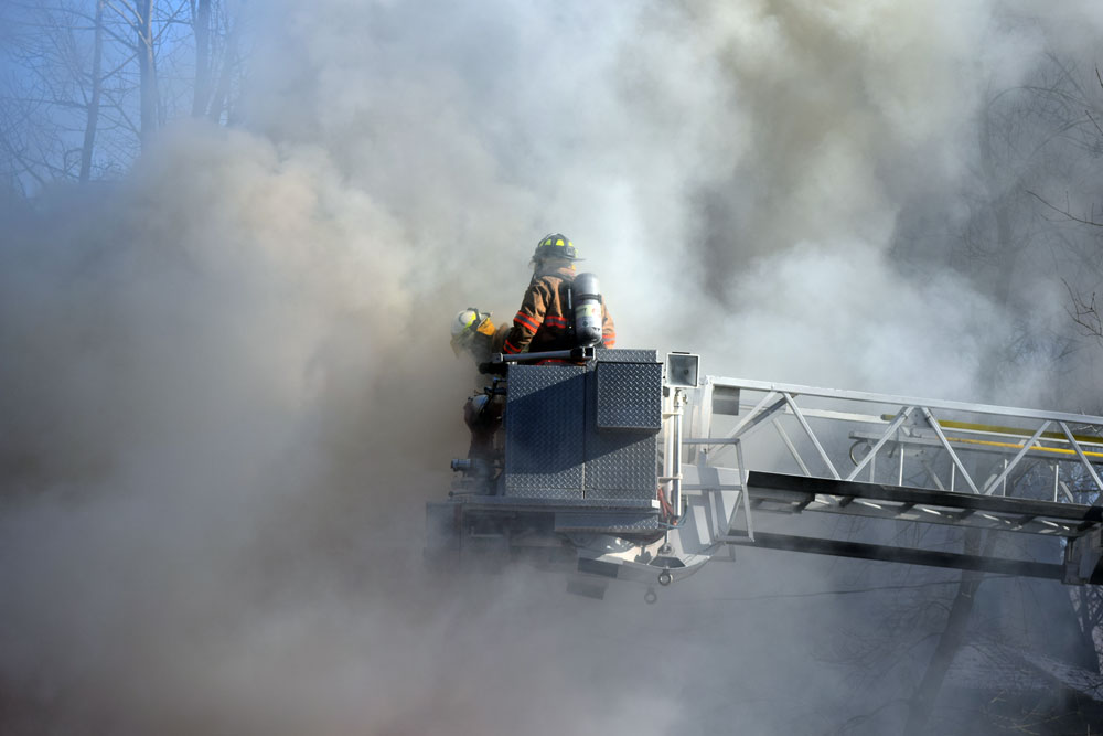 Smoke envelops a pair of firefighters as they stand on the platform of the Saranac Lake Volunteer Fire Department's aerial truck during a fire on Lake Street Monday morning. (Enterprise photo — Chris Knight)