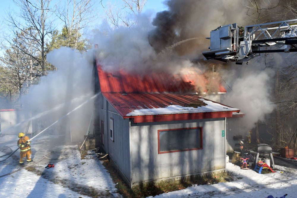 From above and below, firefighters use hoses to pour water onto a burning house at 52 Lake St. in Saranac Lake this morning. (Enterprise photo — Chris Knight)