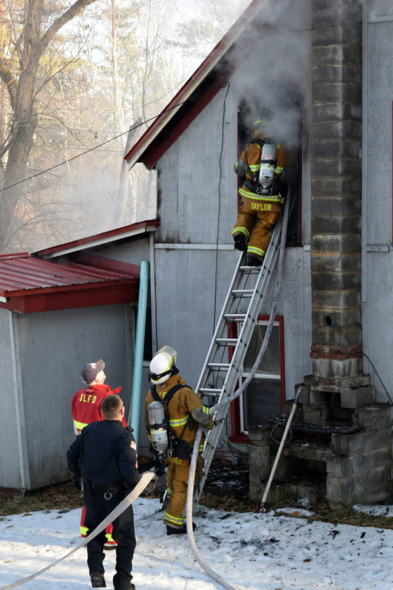 Saranac Lake Volunteer Fire Department Capt. Casey Taylor climbs a ladder carrying a hose into the smoky second-floor window of a house on Lake Street. Monday morning. (Enterprise photo — Chris Knight)