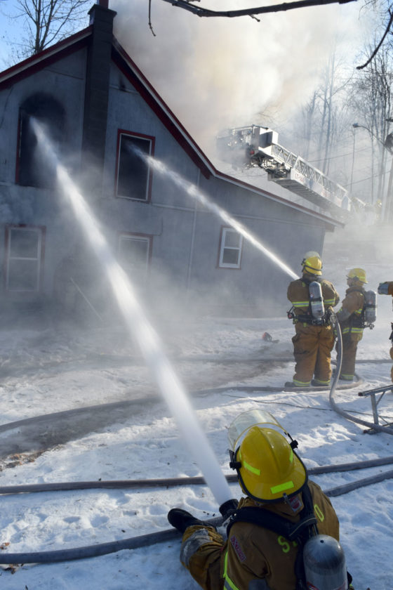 From the ground, firefighters drench the upper floor and attic of a Lake Street house with water Monday morning.  (Enterprise photo — Chris Knight)