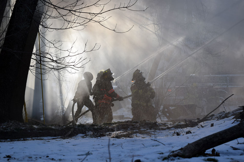 Silhouetted in smoke, firefighters and a state trooper battle a blaze Monday morning at 52 Lake St. in Saranac Lake. (Enterprise photo — Chris Knight)