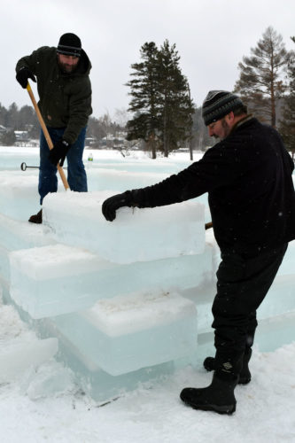 """Sam Churco, right, and Dan Trim guide an ice block into place Friday on one of the corners of the Saranac Lake Winter Carnival Ice Palace, which will have a log-cabin-style look this year to go with the Carnival's """"Adirondack Wildlife"""" theme.  (Enterprise photo — Chris Knight)"""