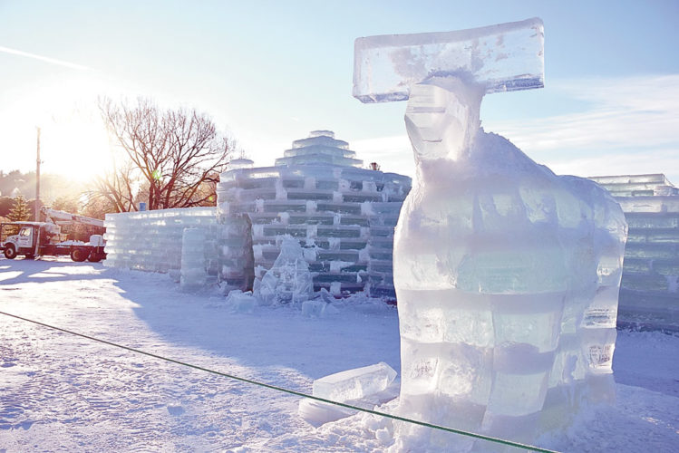 """Robin Johnson's partly carved ice moose stands outside the Ice Palace this morning looking over Lake Flower Avenue in Saranac three days before the start of Winter Carnival. This year's Carnival theme is """"Adirondack Wildlife."""" (Enterprise photo — Justin A. Levine)"""