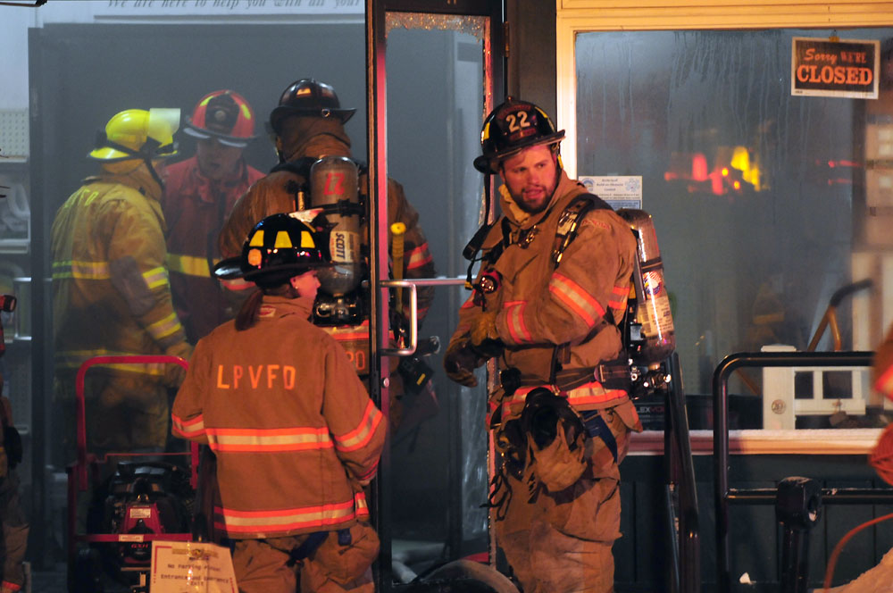 Firefighters from the Lake Placid Volunteer Fire Department work in the front door of Curtis Lumber while battling a blaze that broke out at the business in Ray Brook around 8 p.m. Sunday.  (Enterprise photo — Lou Reuter)