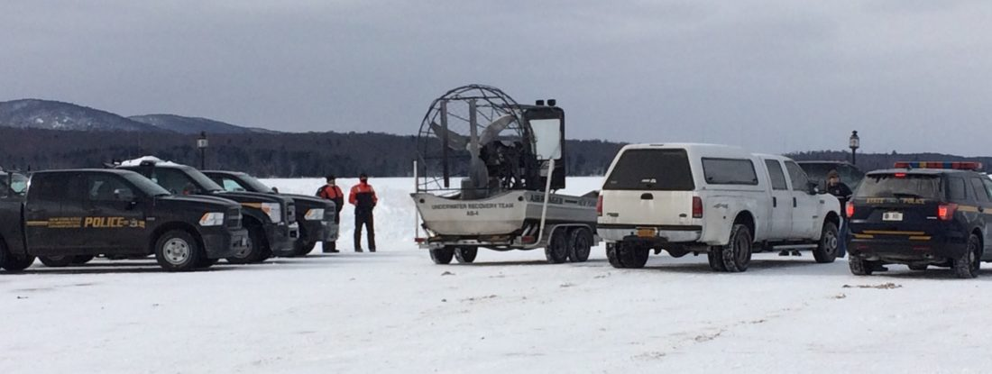 Forest rangers, environmental conservation officers and state police stage Monday in Tupper Lake's Municipal Park on the shore of Raquette Pond while searching for two missing snowmobilers. (Enterprise photo — Justin A. Levine)