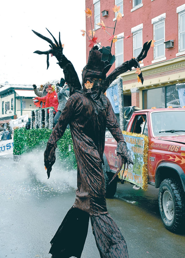 """A tree — possibly an ent, a fictional tree-like creature from J.R.R. Tolkien's """"The Lord of the Rings"""" — walks with the Kiwanis Club of Saranac Lake's float in the parade. (Enterprise photo — Justin A. Levine)"""