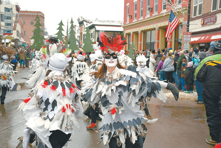 Zoe Smith and the Soma Beats dancers, wearing elaborate snowy owl costumes, boogie down Broadway during Saturday's Saranac Lake Winter Carnival Gala Parade. Soma Beats and Bucket Ruckus teamed up and won the trophy for best independent walking group. (Enterprise photo — Justin A. Levine)