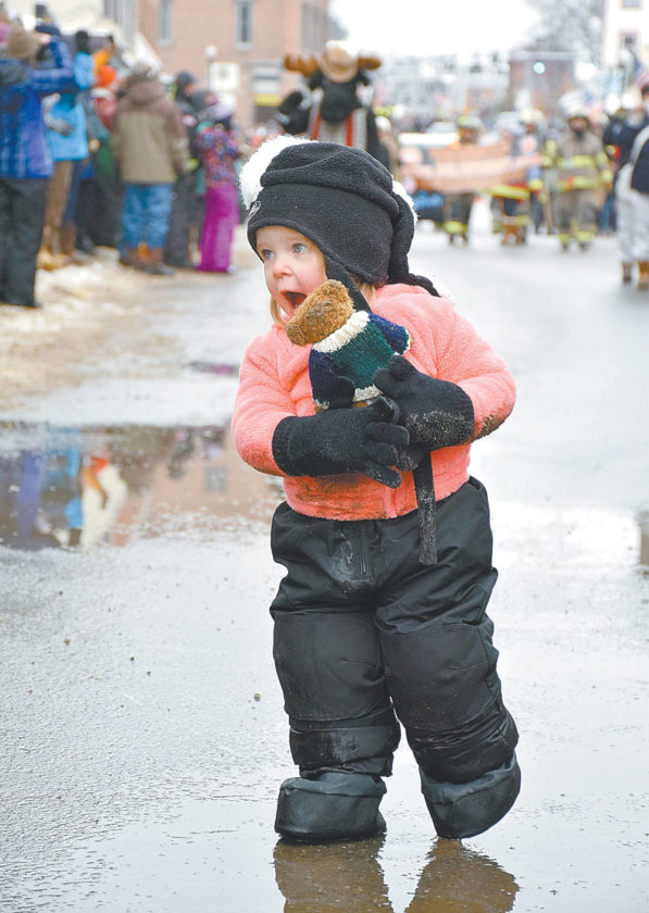 A girl smiles and clutches her teddy bear while walking in the parade. (Enterprise photo — Justin A. Levine)