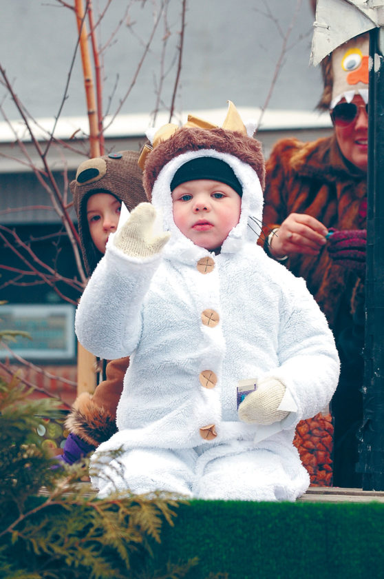 A costumed child waves from a float. (Enterprise photo — Lou Reuter)