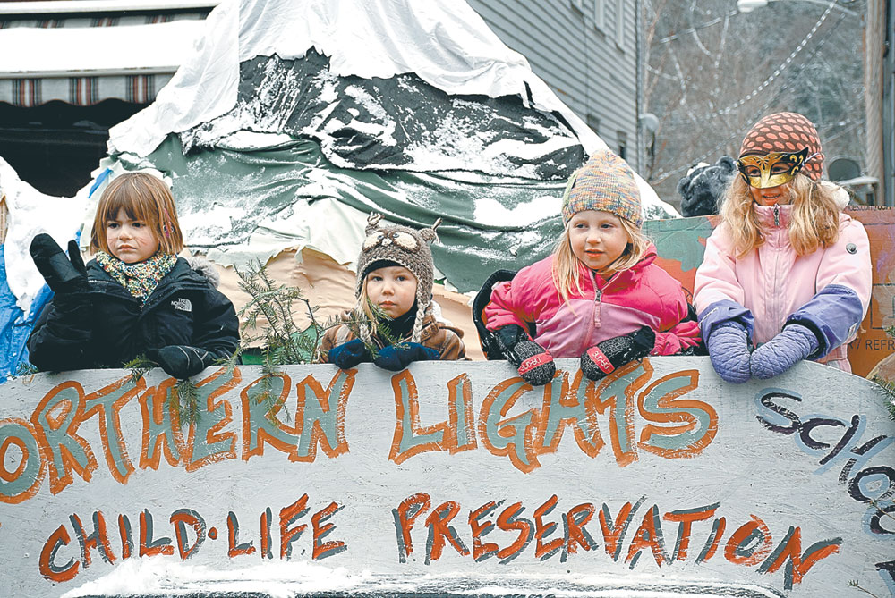 """""""Child-life preservation"""" is the theme of Northern Lights School's float, which included a landscape of snow-capped mountains and cute kids. It won the trophy for best school float. (Enterprise photo — Justin A. Levine)"""