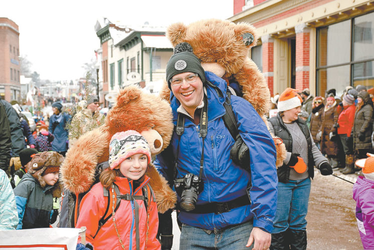 Nelle Aaron and her father Ken carry big teddy bears in backpacks as they march with Petrova Elementary School, which won second place among school walking groups. (Enterprise photo — Justin A. Levine)