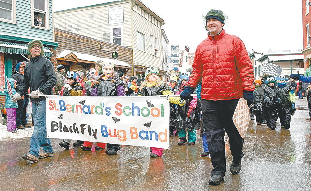 """St. Bernard's School students dressed as insects and played kazoos in a """"Blackfly Bug Band"""" while parents wore bug nets  and carries flyswatters. The Saranac Lake Catholic school won the trophy for the best school walking group. (Enterprise photo — Justin A. Levine)"""