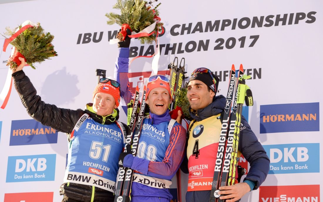 Lowell Bailey celebrates his gold-medal victory in the 20-kilometer individual raceThursday at the biathlon world championships in Hochfilzen, Austria. Ondrej Moravec of the Czech Republic, left, took silver and France's Martin Fourcade won bronze. (Photo — NordicFocus/US Biathlon)