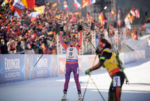 Susan Dunklee crosses the finish line to capture the silver medal in the 12.5-kilometer mass start Sunday at the world championships in Hochfilzen, Austria. (Photo — NordicFocus/US Biathlon)