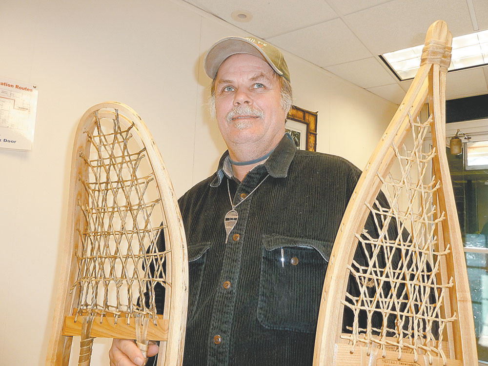 Brian Theriault of Fort Kent, Maine, displays snowshoes he made that are almost as tall as he is Wednesday at the Enterprise office in Saranac Lake. (Enterprise photo — Peter Crowley)