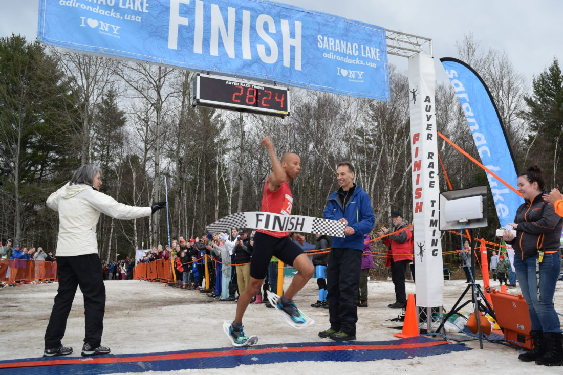 Joseph Gray of Colorado crosses the finish line to claim the World Snowshoe Championships title Saturday at Dewey Mountain Recreation Center in Saranac Lake. (Enterprise photo -- Chris Knight)