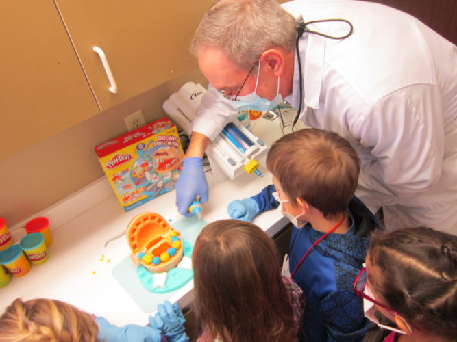 Dr. Murray D.D.S. uses a Play-Doh kit to show Petrova Elementary first graders what his office, Family Smiles Dental Care, does to help patients keep their smiles healthy.  (Photo provided — Diane Chase)